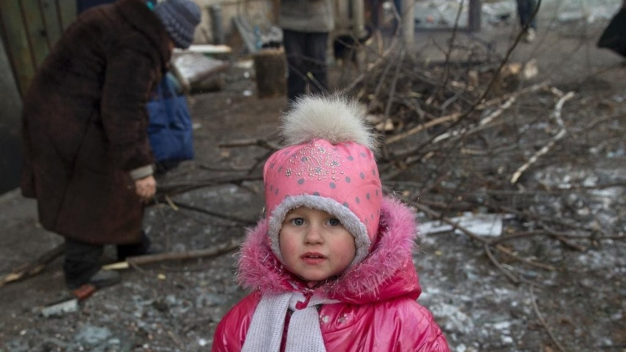Dorina, 3 years-old, stands while an elderly woman picks tree branches for fire, in Debaltseve, Ukraine, Friday, Feb. 20, 2015. After weeks of relentless fighting, the embattled Ukrainian rail hub of Debaltseve fell Wednesday to Russia-backed separatists, who hoisted a flag in triumph over the town. The Ukrainian president confirmed that he had ordered troops to pull out and the rebels reported taking hundreds of soldiers captive.(AP Photo/Vadim Ghirda)