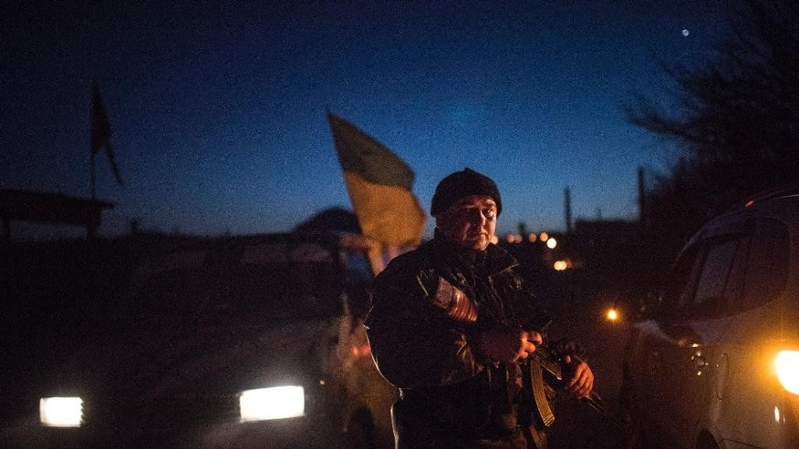 A Ukrainian serviceman guards a checkpoint in Severodonetsk, eastern Ukraine, Saturday, Feb. 21, 2015.Ukrainian military and separatist representatives exchanged dozens of prisoners under cover of darkness at a remote frontline location Saturday evening, kicking off a process intended to usher in peace to the conflict-ridden east. (AP Photo/Evgeniy Maloletka)