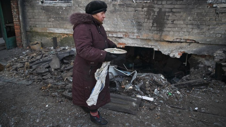 Yevgeniya Fomichova, 60, carries food she cooked outside a damaged apartment building in Debaltseve, Ukraine, Friday, Feb. 20, 2015. After weeks of relentless fighting, the embattled Ukrainian rail hub of Debaltseve fell Wednesday to Russia-backed separatists, who hoisted a flag in triumph over the town. The Ukrainian president confirmed that he had ordered troops to pull out and the rebels reported taking hundreds of soldiers captive. (AP Photo/Vadim Ghirda)