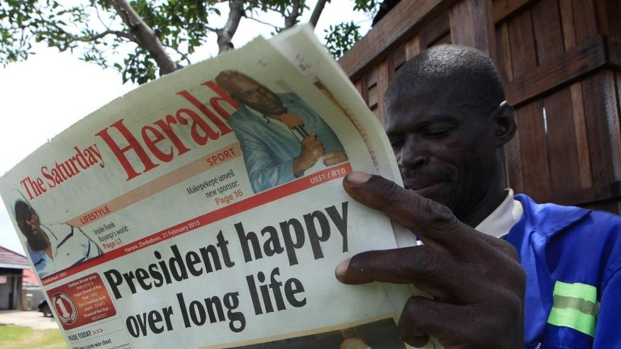 A man reads the state owned newspaper, The Herald, in Harare, Saturday, Feb, 21, 2015.  Mugabe marks his 91st birthday Saturday with his supporters saying they will back him to run his full term until 2018 and beyond despite nagging questions about his health and an economy that is crumbling under his watch. (AP Photo/Tsvangirayi Mukwazhi)