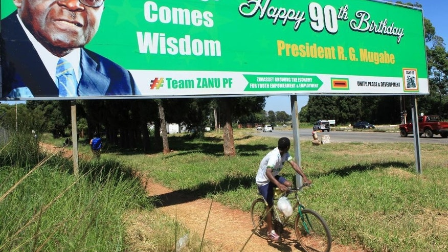 In this photo taken Friday, Feb. 20, 2015, a man cycles beneath a year-old billboard from last year wishing Zimbabwean President Robert Mugabe a happy 90th birthday in Harare.  Mugabe marks his 91st birthday Saturday Feb, 21, 2015 with his supporters saying they will back him to run his full term until 2018 and beyond despite nagging questions about his health and an economy that is crumbling under his watch. (AP Photo/Tsvangirayi Mukwazhi)