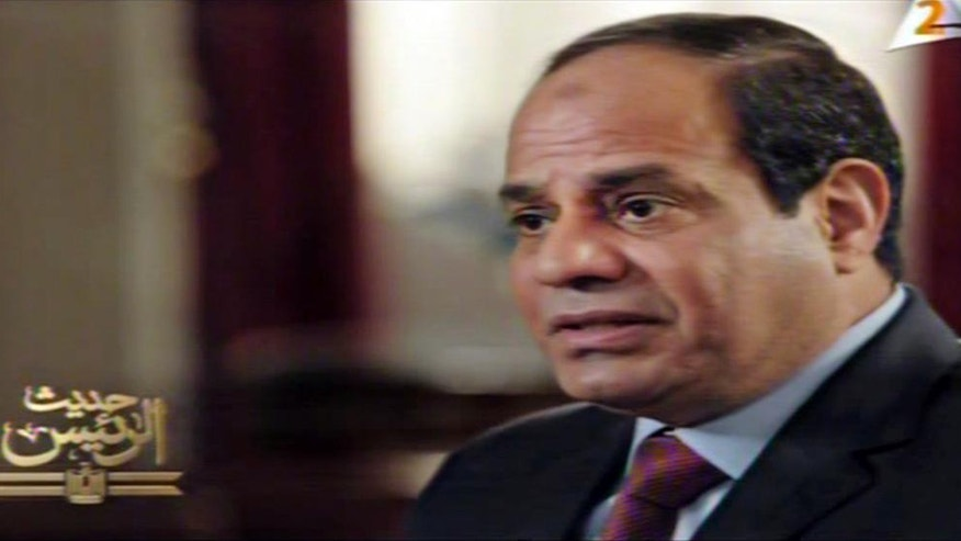 """In this image taken from Egypt State TV, Egyptian President Abdel-Fattah el-Sissi speaks in a television address broadcast Sunday, Feb. 22, 2015. Sissi said the need for a joint Arab military force is growing every day as the region is faced with the threat of Islamic militancy. The Egyptian leader said both Jordan and the United Arab Emirates have offered to dispatch troops to aid Egypt following last week's beheading in Libya of 21 Egyptian Coptic Christians by Islamic State militants. Logo on left in Arabic reads, """"The speech of the President."""" (AP Photo/Egypt State TV)"""
