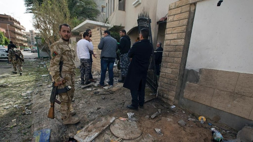 "Security Personnel inspect the Iranian ambassador's house after it received minor damage from an improvised explosive device placed among garbage bags, in Tripoli, Libya, Sunday, Feb. 22, 2015. Iran's Foreign Ministry spokeswoman Marzieh Afkham condemned the ""terrorist"" attack, which she said claimed no lives. She called on political rivals in Libya to form a national unity government to end the country's escalating chaos. (AP Photo/Mohamed Ben Khalifa)"