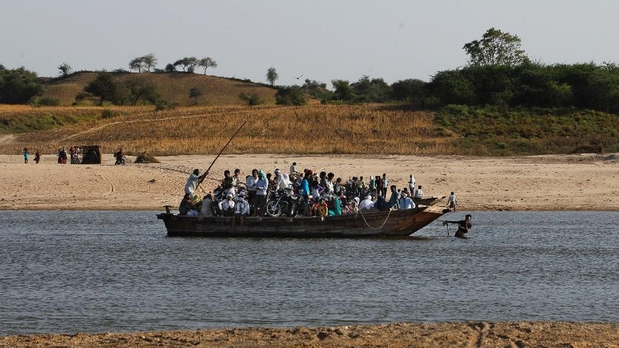 In this photo taken Monday, April 28, 2014, Indian villagers cross the River Chambal on a ferry near Bhopepura village in the northern Indian state of Uttar Pradesh. A narrow 250-mile stretch of the Chambal was declared an official sanctuary in the late 1970s, a sanctuary of crocodiles and jackals, river dolphins and the occasional wolf. But with India's economic growth came troubles that threaten the Chambal and its wildlife: polluting factories, illegal sand mining and fish poachers who hack at gharials with axes when the animals get tangled in their nets. (AP Photo/Altaf Qadri)