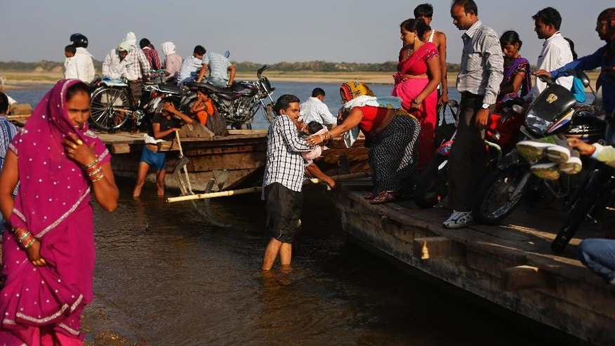 In this photo taken Monday, April 28, 2014, Indian villagers alight from a ferry after crossing the River Chambal near Bhopepura village in the northern Indian state of Uttar Pradesh. A narrow 250-mile stretch of the Chambal was declared an official sanctuary in the late 1970s, closing it to everyone but longtime villagers, approved scientists and the handful of tourists who make it here. But with India's economic growth came troubles that threaten the Chambal and its wildlife: polluting factories, illegal sand mining and fish poachers who hack at gharials with axes when the animals get tangled in their nets. (AP Photo/Altaf Qadri)