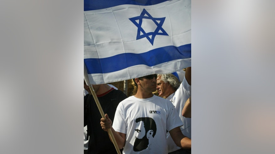 FILE - In this May 1, 2007 file photo, an Israeli, wearing a shirt with an image of Theodor Herzl, the founder of modern Zionism, carries a national flag as he marches in a protest near Jerusalem. What is Zionism? The seemingly antiquated philosophical question has gained urgency in an Israeli election campaign where the liberal opposition has rebranded itself as the Zionist Union in a bid to take votes from the nationalist right of Prime Minister Benjamin Netanyahu -- sparking a debate about Israel's place in the world and setting the stage for a surprisingly climactic vote. (AP Photo/Sebastian Scheiner, File)