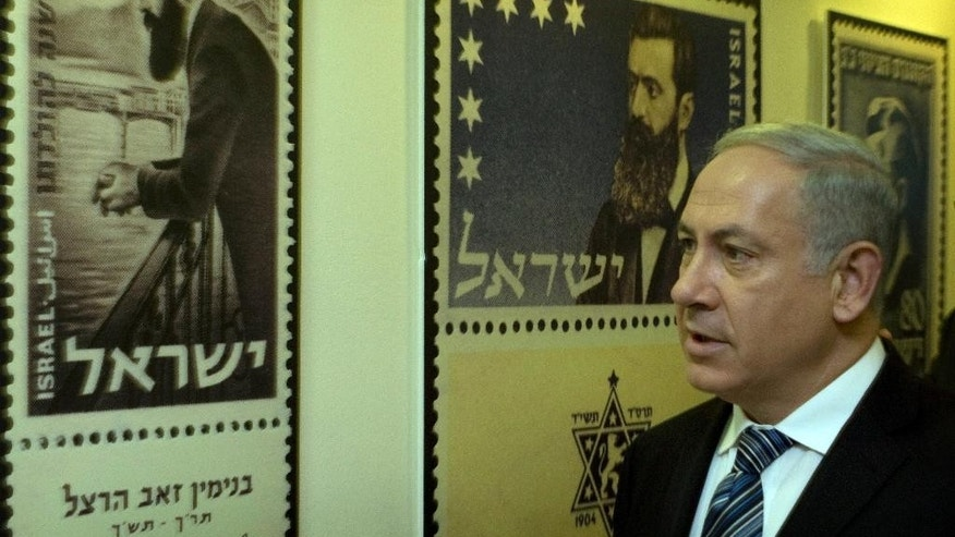 FILE - In this April 18, 2010 file photo, Israeli Prime Minister Benjamin Netanyahu looks at posters of stamps carrying the portrait of Theodor Herzl, the founder of modern Zionism, in Jerusalem. What is Zionism? The seemingly antiquated philosophical question has gained urgency in an Israeli election campaign where the liberal opposition has rebranded itself as the Zionist Union in a bid to take votes from the nationalist right of Prime Minister Benjamin Netanyahu -- sparking a debate about Israel's place in the world and setting the stage for a surprisingly climactic vote. (AP Photo/Sebastian Scheiner, Pool, File)