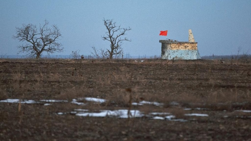 The former Soviet Union flag flies on top of a construction in a field, near Zholobok, Ukraine, Saturday, Feb. 21, 2015. Ukrainian military and separatist representatives exchanged dozens of prisoners under cover of darkness at a remote frontline location Saturday evening, kicking off a process intended to usher in peace to the conflict-ridden east. Ukrainian troops and rebels were exchanged, according to a separatist official overseeing the prisoner swap at a no man's land location near the village of Zholobok, some 20 kilometers (12 miles) west of the rebel-held city Luhansk. (AP Photo/Vadim Ghirda)