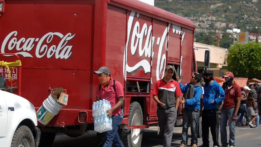 In this Nov. 4, 2014 photo, masked protesters begin to empty a Coca-Cola distribution truck in the city of Chilpancingo, Mexico. Coca-Cola Femsa SA, the brand's largest bottler in Mexico, has temporarily suspended operations in the capital of the embattled state of Guerrero following attacks on its workers and its trucks. The decision comes amid protests in the southern state around the disappearance of 43 students. Protesting students and teachers have regularly blockaded roads and taken over vehicles delivering everything from milk to snacks. (AP Photo/Alejandrino Gonzalez)