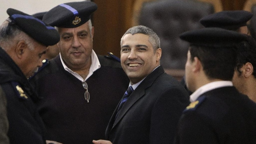 Canadian Al-Jazeera English journalist Mohamed Fahmy, speaks with Egyptian policemen during his retrial in Cairo, Egypt, Monday, Feb. 23, 2015. The retrial of two Al-Jazeera English journalists who face terror-related charges in a case widely criticized by human rights organizations and media groups has been postponed to March 8. (AP Photo/Amr Nabil)