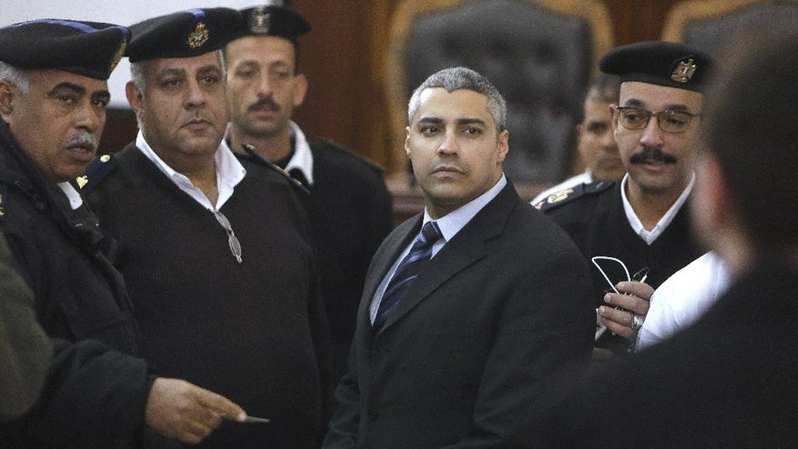 Canadian Al-Jazeera English journalist Mohamed Fahmy, speaks with policemen during his retrial in Cairo, Egypt, Monday, Feb. 23, 2015. The retrial of two Al-Jazeera English journalists who face terror-related charges in a case widely criticized by human rights organizations and media groups has been postponed to March 8. (AP Photo/Amr Nabil)