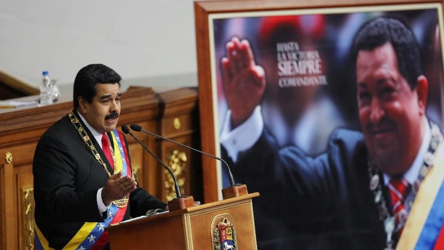 FILE - In this Jan. 21, 2015 file photo, Venezuela's President Nicolas Maduro delivers his annual state-of-the-nation address beside a framed poster featuring the late President Hugo Chavez, at the National Assembly in Caracas, Venezuela. While the arrest of Caracas Mayor Antonio Ledezma in Feb. 2015 provoked spontaneous demonstrations and drew international condemnation, it also reminded many Venezuelans of what they most disliked about the politicians who preceded Maduro and his late mentor Hugo Chavez at a time when the socialist government faces an economic crisis that has sent the president's popularity plummeting. (AP Photo/Ariana Cubillos, File)