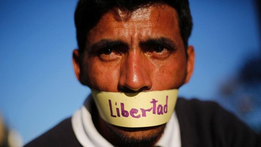 """In this Friday, Feb. 20, 2015 photo, a protester with his mouth taped shut and a message that reads in Spanish; """"Freedom,"""" attends a demonstration demanding the release of Mayor Antonio Ledezma, in Caracas, Venezuela. Demonstrators are condemning Thursday night's surprise arrest of the Caracas' mayor for allegedly plotting to overthrow the government of President Nicolas Maduro. Late Thursday Maduro said that Ledezma, one of the most vocal opposition leaders, would be punished for trying to sow unrest in Venezuela. (AP Photo/Ariana Cubillos)"""