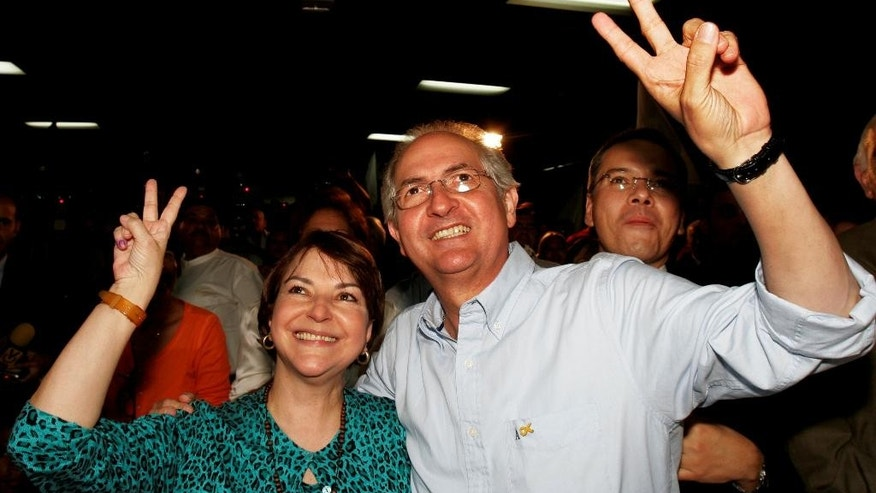 FILE - In this Nov. 26, 2008 file photo, Caracas' newly elected mayor Antonio Ledezma and his wife Mitzy Capriles gesture to supporters and the press in Caracas, Venezuela. Ledezma was arrested in Feb. 2015 by the government of President Nicolas Maduro while holding same post that he won in 2013 elections. Maduro has seized on Ledezma's relationship with disgraced former President Carlos Andres Perez to accuse the 59-year-old politician of being a relic of the so-called Fourth Republic, a term created by Hugo Chavez to describe a sham, elite-dominated democracy that excluded the poor decades before Chavez was elected president in 1999 and began moving the country to the left. (AP Photo/Carlos Hernandez, File)