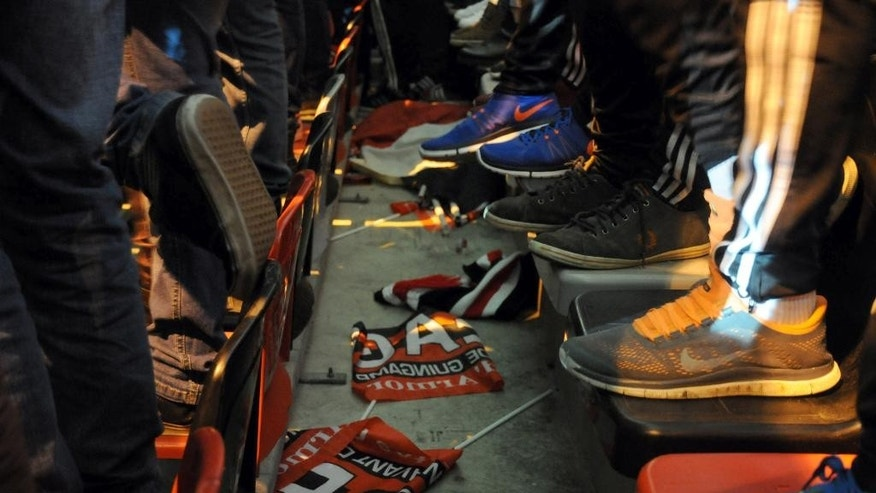 In this photo dated Thursday, Feb. 19, 2015,  Guingamp flags litter the floor between seats that fans at the Roudourou stadium in Guingamp, western France, are standing on to watch the club beat Dynamo Kiev 2-1 in the Europa League.  With one of the puniest budgets in France's top division, Guingamp can't splash the cash like some of the mammoths — Qatar-owned Paris Saint-Germain being the prime example — it competes against and humbles from time to time. (AP Photo/John Leicester)