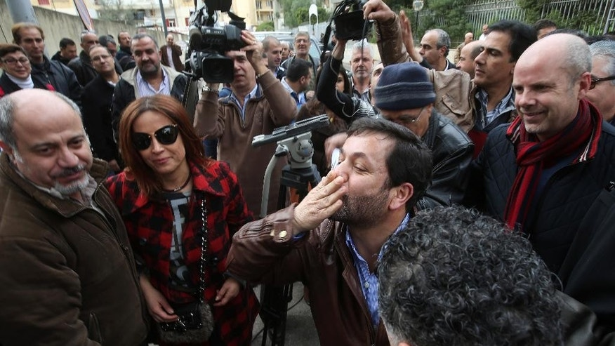 Lebanese satirist Charbel Khalil, center, sends kisses to his supporters after he appeared before a prosecutor at the judicial palace in Beirut, Lebanon, Monday, Feb 23, 2015. The Lebanese satirist has appeared before a prosecutor in Beirut after the country's top Sunni religious authority filed a judicial complaint against him for allegedly defaming Islam. Khalil found himself in hot water after he shared a photo on social media earlier this week that was viewed by some as insulting of Islam. (AP Photo/Hussein Malla)