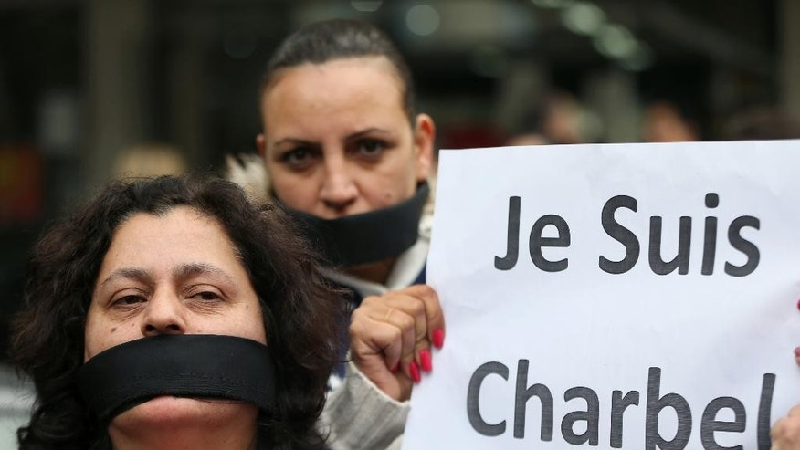 "Supporters of Lebanese satirist Charbel Khalil cover their mouths with black cloth and hold a French placard that reads: ""we are Charbel,"" as they protest outside the judicial palace in Beirut, Lebanon, Monday, Feb 23, 2015. The Lebanese satirist has appeared before a prosecutor in Beirut after the country's top Sunni religious authority filed a judicial complaint against him for allegedly defaming Islam. Khalil found himself in hot water after he shared a photo on social media earlier this week that was viewed by some as insulting of Islam. (AP Photo/Hussein Malla)"
