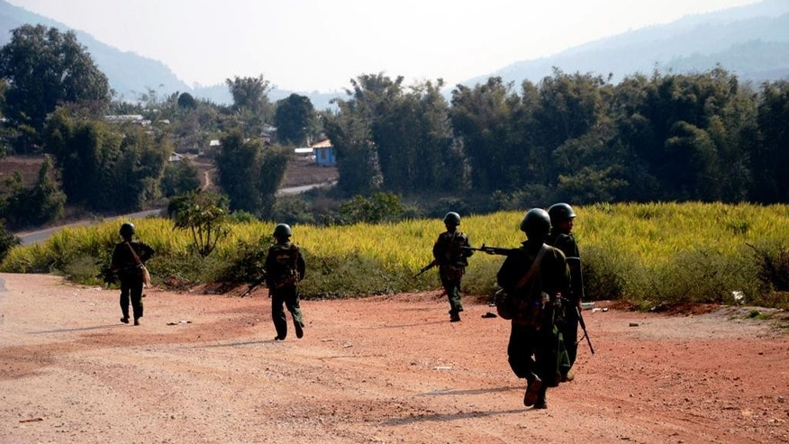 In this Feb. 17, 2015, photo provided by the Eleven Media Group, Myanmar army soldiers carrying weapons patrol on a road in Kokang, northeastern Shan State, more than 800 kilometers (500 miles) northeast of Yangon, Myanmar.  Fighting between Myanmar troops and ethnic Kokang rebels near the Chinese border has left more than 130 dead since the clashes started Feb. 9. (AP Photo/Eleven Media Group)