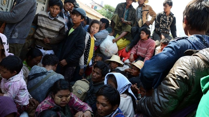 In this Feb. 17, 2015, photo provided by the Eleven Media Group, refugees wait for a Myanmar Red-Cross Team during a clash between government troops and Kokang rebels in Kokang, northeastern Shan State, more than 800 kilometers (500 miles) northeast of Yangon, Myanmar. Fighting between Myanmar troops and ethnic Kokang rebels near the Chinese border has left more than 130 dead since the clashes started Feb. 9. (AP Photo/Eleven Media Group)