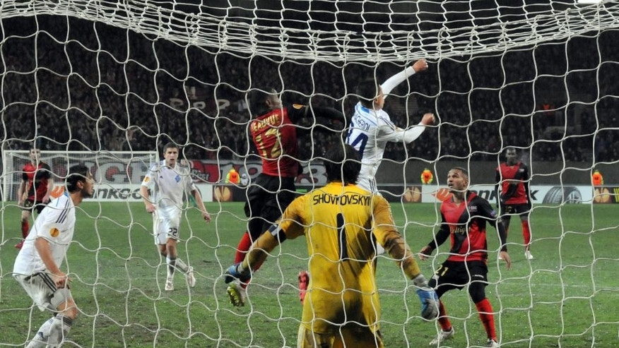 In this photo dated Thursday, Feb. 19, 2015, Dynamo Kiev goalkeeper Olexandr Shovkovskiy, center, prepares to pounce as players scramble for the ball in front of his goal in the Roudourou stadium, in Guingamp, western France, during Guingamp's 2-1 victory in the Europa League.  With one of the puniest budgets in France's top division, Guingamp can't splash the cash like some of the mammoths — Qatar-owned Paris Saint-Germain being the prime example — it competes against and humbles from time to time. (AP Photo/John Leicester)