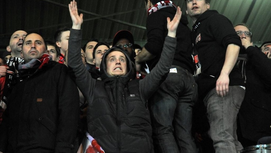 In this photo dated Thursday, Feb. 19, 2015, a Guingamp fan in the Roudourou stadium in Guingamp, western France, gesticulates as he watches the club beat Dynamo Kiev 2-1 in the Europa League.  With one of the puniest budgets in France's top division, Guingamp can't splash the cash like some of the mammoths — Qatar-owned Paris Saint-Germain being the prime example — it competes against and humbles from time to time. (AP Photo/John Leicester)