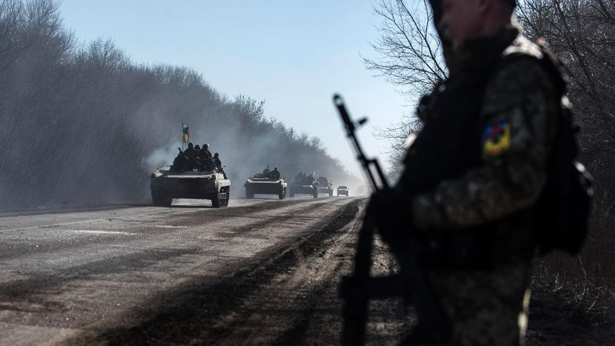 Ukrainian troops ride on armoured vehicles near Artemivsk, eastern Ukraine, Tuesday, Feb. 24, 2015. Ukrainian officials said they haven't yet started pulling heavy weapons back from a frontline in eastern Ukraine because of continued rebel violations of a cease-fire deal. (AP Photo/Evgeniy Maloletka)