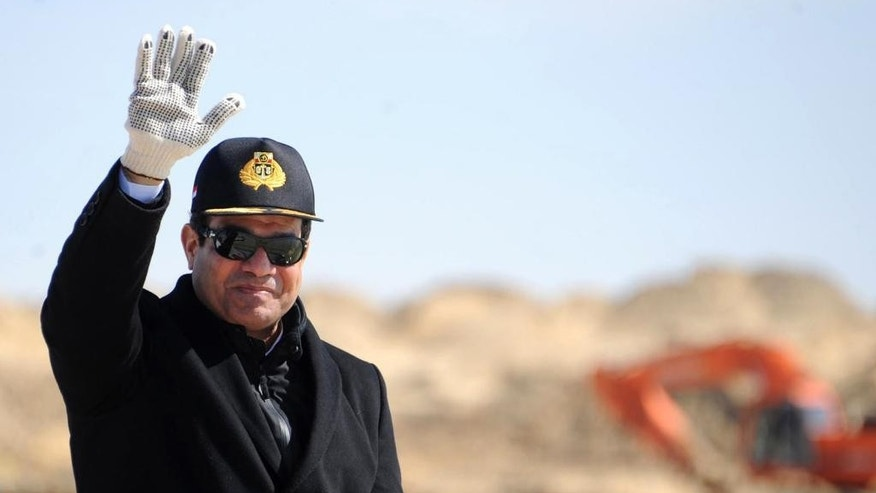 "In this Sunday, Feb. 22, 2015 file photo released by the Egyptian Presidency, Egyptian President Abdel-Fattah el-Sissi, right, waves during a visit to the Suez Canal in Ismailia, Egypt. El-Sissi issued a law that broadens the state's definition of terrorism to include anyone who threatens public order ""by any means,"" and gives authorities powers to draw up lists of alleged terrorists with little judicial recourse. The legislation was signed in the form of a decree last week and was distributed to reporters on Tuesday, Feb. 24, 2015. El-Sissi has the power to approve new laws in the form of decrees. (AP Photo/Egyptian Presidency)"