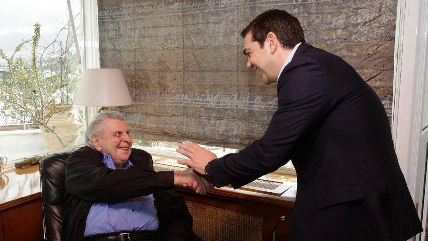 Greece's Prime Minister Alexis Tsipras, right, shakes hands with Greek composer Mikis Theodorakis during their meeting in Athens, Tuesday, Feb. 24, 2015. Tsipras is facing dissent within his left-wing Syriza party over claims it is backtracking on its recent election-winning promises to ease budget cuts for the recession-battered Greeks.(AP Photo/Orestis Panagiotou, Pool)