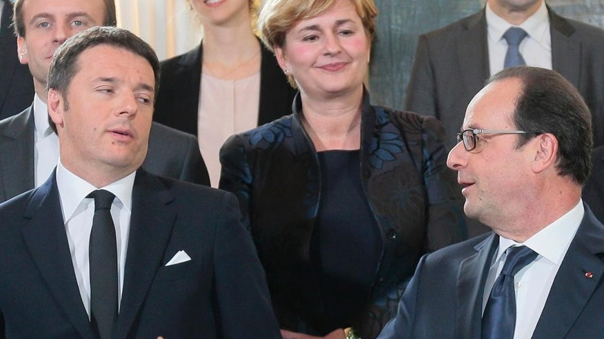 Italian Prime Minister Matteo Renzi, left, watches French President Francois Hollande gesturing during a family picture as part of a French-Italian summit at the Elysee Palace, Tuesday, Feb. 24, 2015 in Paris (AP Photo/Jacques Demarthon, Pool)