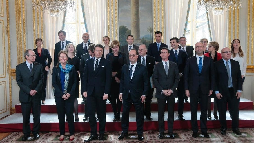From the left, front row, Italian Economy and Finance Minister Pier Carlo Padoan, French Environment Minister Segolene Royal, Italian Prime Minister Matteo Renzi, French President Francois Hollande, French Prime Minister Manuel Valls, Italian Interior Minister Angelino Alfano and French Finance Minister Michel Sapin  pose for a picture during a French-Italian summit at the Elysee Palace, Tuesday, Feb. 24, 2015 in Paris (AP Photo/Jacques Demarthon, Pool)