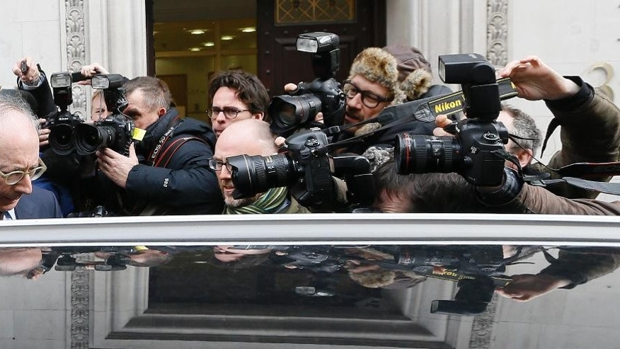 Conservative Party lawmaker Malcolm Rifkind, left, is surrounded by the media in Westminster, London, Tuesday, Feb. 24, 2015. Malcolm Rifkind quit Tuesday as head of the committee overseeing Britain's intelligence services and announced his retirement from Parliament, after being caught in a hidden-camera sting appearing to discuss swapping political influence for money. (AP Photo/Kirsty Wigglesworth)
