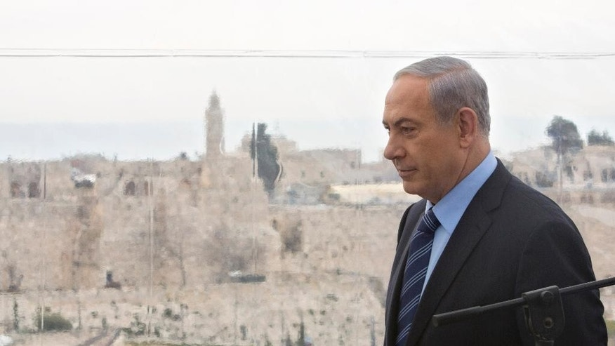 File: In this Monday, Feb. 23, 2015 file photo Israeli Prime Minister Benjamin Netanyahu walks past a window overlooking the Old City of Jerusalem. According to files after allegedly being leaked and widely published Tuesday Feb. 24, 2015, documenting the concerns of past South African authorities' concerns about Iranian influence in Africa as well as communication between South African intelligence and the American CIA and Israel's Mossad. (AP Photo/Sebastian Scheiner, FILE)