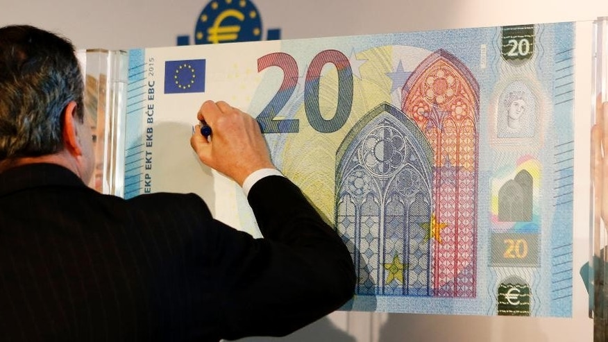 President of European Central Bank Mario Draghi signs a facsimile of the new 20 Euro banknote in Frankfurt, Germany, Tuesday, Feb. 24, 2015. (AP Photo/Michael Probst)