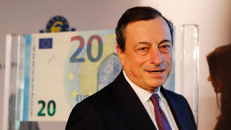 President of European Central Bank Mario Draghi stands next to a facsimile of the new 20 euro banknote in Frankfurt, Germany, Tuesday, Feb. 24, 2015. (AP Photo/Michael Probst)