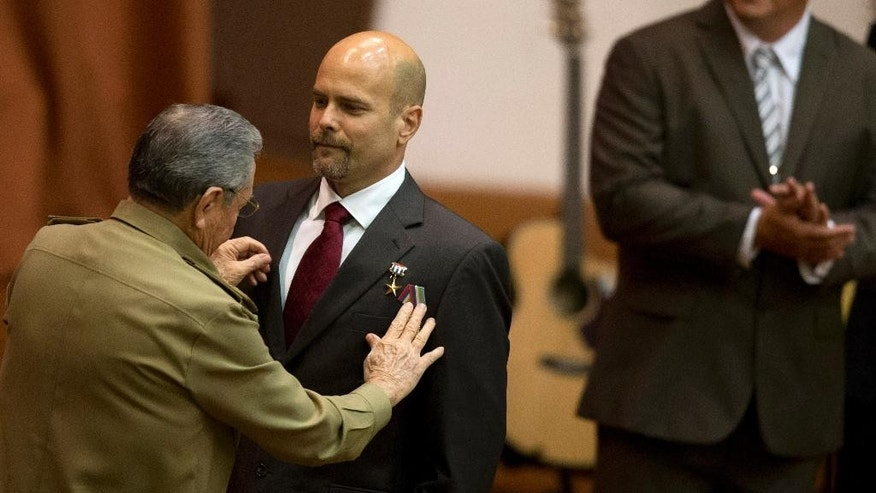 "Cuba's President Raul Castro pins a medal on Gerardo Hernandez , as fellow agent Ramon Labanino, background, applauds during a medal ceremony, in Havana, Cuba, Tuesday, Feb. 24, 2015. Castro honored the agents known as the ""Cuban Five,"" who spent years in U.S. prisons, becoming heroes in their homeland and causing friction between the two countries that are now in the process of restoring full diplomatic relations. (AP Photo/Ramon Espinosa)"