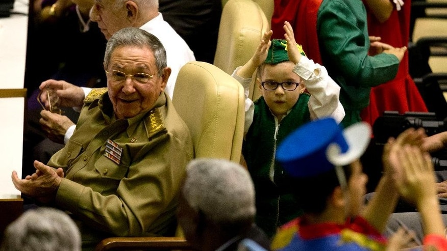 Cuba's President Raul Castro, left, smiles during a medal ceremony, in Havana, Cuba, Tuesday, Feb. 24, 2015. Castro honored five Cuban intelligence agents who spent years in U.S. prisons, becoming heroes in their homeland and causing friction between the two countries that are now in the process of restoring full diplomatic relations. (AP Photo/Ramon Espinosa)