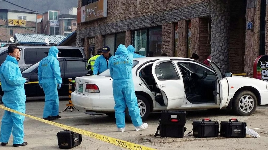 South Korean police officers investigate a vehicle near the scene of an incident in Sejong, south of Seoul, South Korea, Wednesday, Feb. 25, 2015. South Korean police said Wednesday that three people were dead after a gunman opened fire at a store in Sejong City and set the store on fire before fleeing. (AP Photo/Yonhap, Lee Jae-lim) KOREA OUT