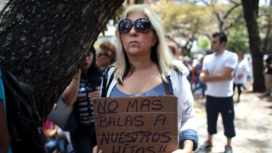 "A protester holds a sign that reads in Spanish ""No more bullets at our children"" during a demonstration against violence outside the Vatican's diplomatic mission in Caracas, Venezuela, Wednesday, Feb. 25, 2015. Protesters are asking Pope Francis to intervene after the death of a 14-year-old student who died after he was shot in the head Tuesday at an anti-government protest in the city of San Cristobal. (AP Photo/Ariana Cubillos)"