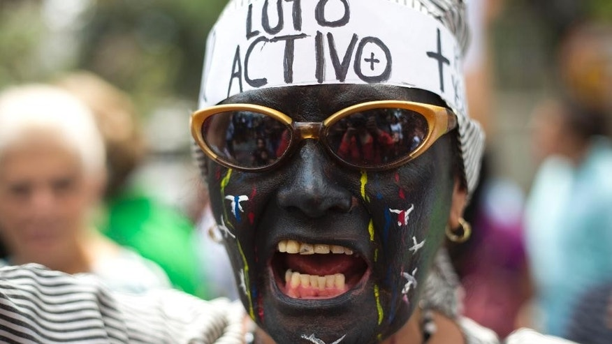 "A protester with her face painted and wearing the words in Spanish: ""In active mourning"" screams outside the Vatican's diplomatic mission during a protest against violence in Caracas, Venezuela, Wednesday, Feb. 25, 2015. Protesters gathered here to ask Pope Francis to intervene after the death of a 14-year-old boy who was shot in the head Tuesday at an anti-government protest in the city of San Cristobal. (AP Photo/Ariana Cubillos)"