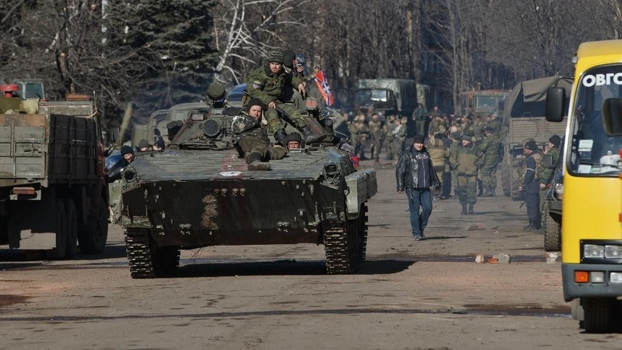 Russia-backed rebels ride on an armored vehicle in the center of Debaltseve, Ukraine, Monday, Feb. 23, 2015. After weeks of relentless fighting, the embattled Ukrainian rail hub of Debaltseve fell last week to Russia-backed separatists. (AP Photo/Vadim Ghirda)