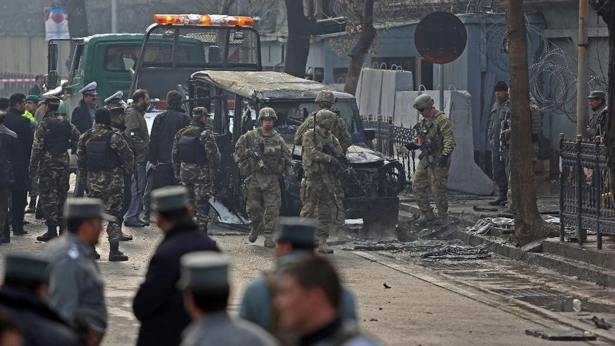 NATO and Afghan security personal inspect a damaged vehicle at the site of a suicide attack in Kabul, Afghanistan, Thursday, Feb. 26, 2015. A suicide bomber driving a car packed with explosives targeted a Turkish Embassy vehicle near the Iranian Embassy in the Afghan capital during the Thursday morning rush hour.(AP Photo/Rahmat Gul)
