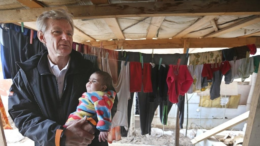 Jan Egeland, the secretary general of the Norwegian Refugee Council and former U.N. humanitarian chief, holds a Syrian baby during his visit to a refugee camp in the town of Marej  in the Bekaa valley, east Lebanon, Wednesday, Feb. 25, 2015. Egeland, the head of the prominent humanitarian relief organization, told the Associated Press in an interview that UN Security Council resolutions seeking to boost humanitarian access to reach millions of Syrians in desperate need of help have had no effect. (AP Photo/Hussein Malla)