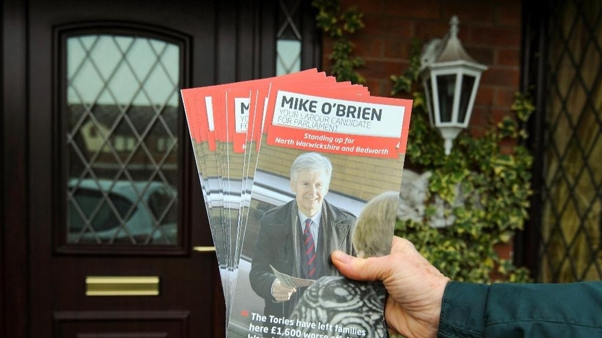 In this photo taken on Friday, Feb. 20, 2015, a Labour activist poses as he delivers pamphlets while canvassing in Wood End, England, ahead of May's General Election. The candidates are busy campaigning, but this is the election that no one is going to win _ and that many voters feel they have already lost. Britain's upcoming election is the most unpredictable in decades. Barring a seismic shift, no party will win a majority in Parliament on May 7, and the deciding hand in forming a government could be held by Scottish nationalists who want to break up Britain or Euroskeptics who seek to abandon the European Union. With the race too close to call in scores of constituencies, every vote really does matter. (AP Photo/Rui Vieira)