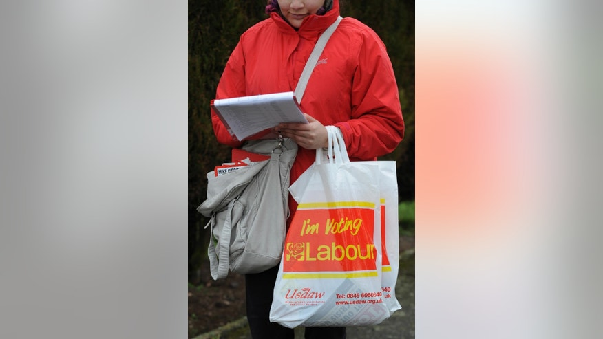 In this photo taken on Friday, Feb. 20, 2015, a Labour activist carries pamphlets while canvassing in Wood End, England, ahead of May's General Election. British voters go to the polls May 7 in the most unpredictable election in decades. All parties are trying to woo voters in the North Warwickshire constituency, one of the country's closest races. (AP Photo/Rui Vieira)