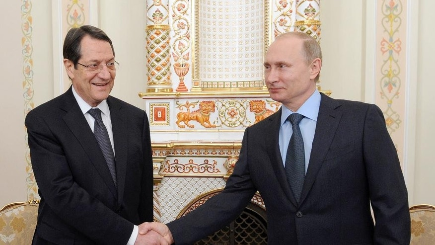 Russian President Vladimir Putin, right, and Cyprus' President Nicos Anastasiades, shake hands at their meeting in the Novo-Ogaryovo residence outside Moscow, Russia, Wednesday, Feb. 25, 2015. (AP Photo/RIA-Novosti, Mikhail Klimentyev, Presidential Press Service)