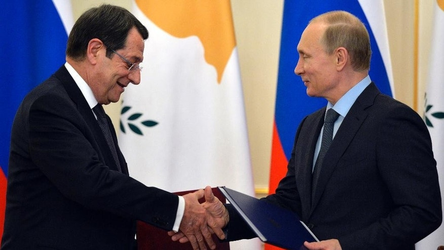 Russian President Vladimir Putin, right, and Cyprus' President Nicos Anastasiades shake hands as they exchange documents at a signing ceremony in the Novo-Ogaryovo residence outside Moscow, Russia, Wednesday, Feb. 25, 2015. Russia and Cyprus have signed a military cooperation agreement that would allow Russian navy ships to make regular port calls on the island. (AP Photo/Yuri Kadobnov, Pool)