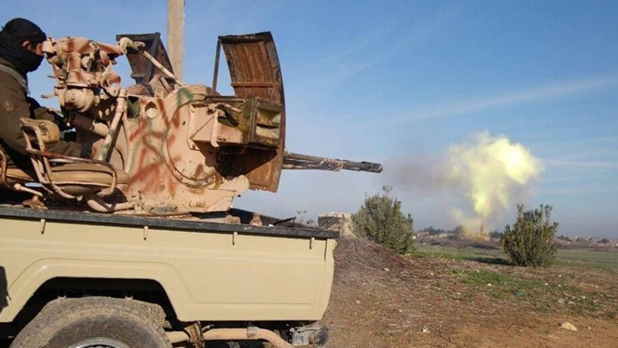 In this image posted on a militant social media account by the Al-Baraka division of the Islamic State group on Tuesday, Feb. 24, 2015, a fighter fires a heavy weapon mounted on the back of a pickup truck during fighting in Tal Tamr, Hassakeh province, Syria. Fierce fighting between Kurdish and Christian militiamen and Islamic State militants is continuing on Wednesday, Feb. 25 in northeastern Syria where the extremist group recently abducted at least 70 Christians. (AP Photo via militant social media account)