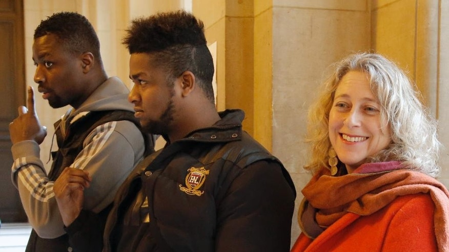 French plaintiffs Amponsah, left, and Elize Novembre stand with Lanna Hollo, senior legal officer with Open Society Justice Initiative, and talk to the media at Paris appeals court, in Paris, France, Wednesday, Feb. 25, 2015. A Paris appeals court is rehearing a racial profiling case brought by 13 men — all black or of North African origin — who claim they've been victims of numerous, unjustified police identity checks because of their ethnicity. (AP Photo/Francois Mori)
