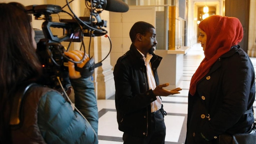Plaintiff Bocar, center, is interviewed by the media at the Paris appeals court in Paris, France, Wednesday, Feb. 25, 2015. A Paris appeals court is rehearing a racial profiling case brought by 13 men — all black or of North African origin — who claim they've been victims of numerous, unjustified police identity checks because of their ethnicity. (AP Photo/Francois Mori)
