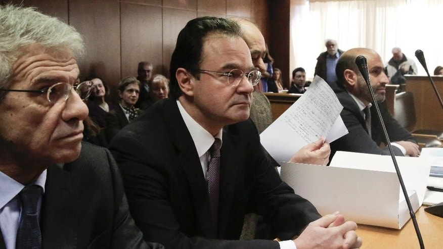 Former Greek finance minister George Papaconstantinou, second left, sits in court next to his lawyers, on Wednesday Feb. 25, 2015 at the start of a criminal trial against him on allegations he removed relatives' names from a list of Greeks holding Swiss bank accounts in HSBC.Papaconstantinou, 53, denies charges that he doctored the document, known in Greece as the Lagarde List, to remove three of his relatives. He was finance minister from late 2009 to mid 2011 and It was under him that Greece signed its first international bailout in May 2010. (AP Photo/Petros Giannakouris)